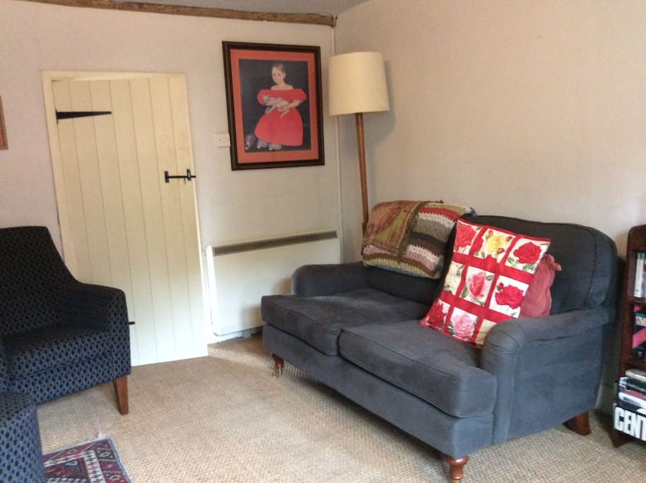 A comfortable, cosy living room with large inglenook fireplace and wood burner.