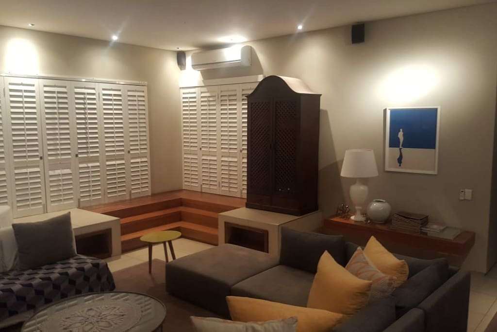 Lounge with shutters and doors that open to let the outdoors inside