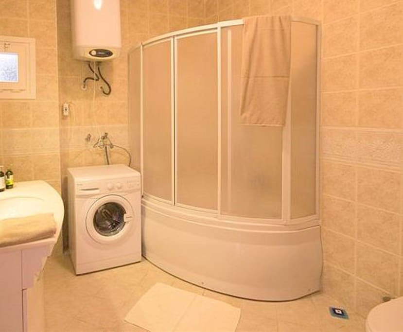 Family bathroom with corner bath, shower and washing machine