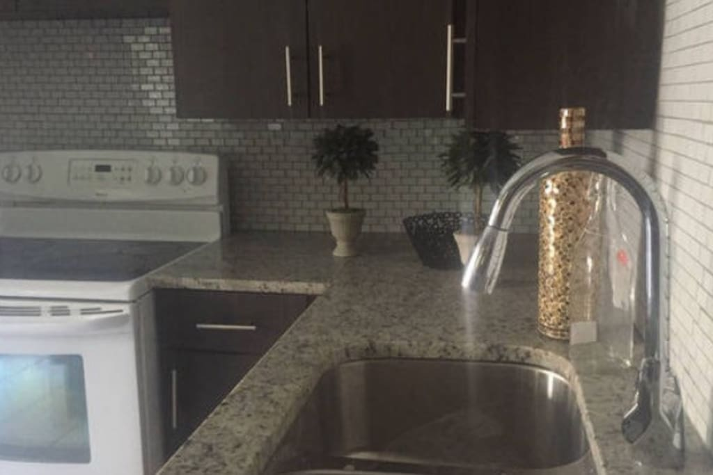 Kitchen                                                       Gorgeous renovated kitchen has granite countertops and glass  tile backsplash                                                  Full size refrigerator  and microwave                                                                      Keurig Coffee Maker    Coffee,sugar,creme included                                             Electric stove/oven                                                             Basic dish ware                                                                            Table seats up to six people