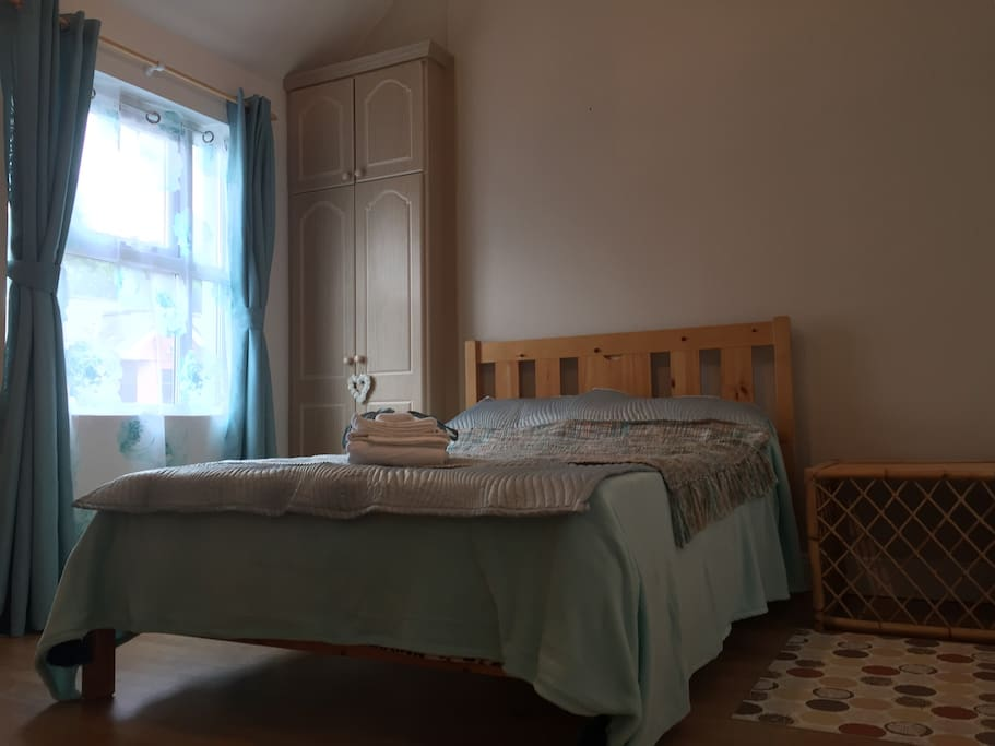 Lovely spacious bedroom with high ceiling and double bed.