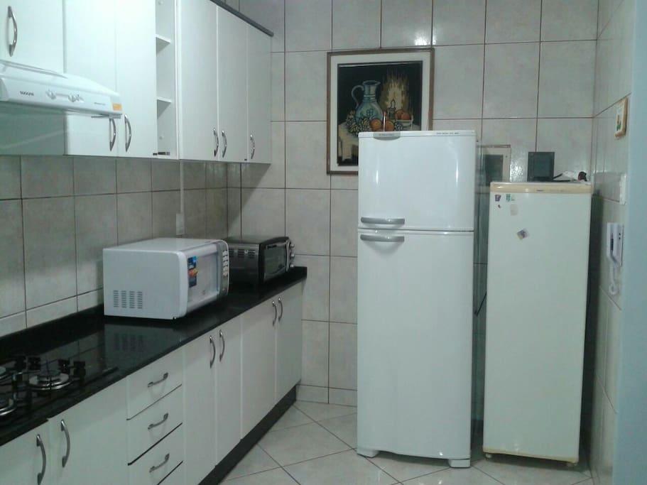 Cozinha com geladeira,freezer, micro-ondas e forninho elétrico.