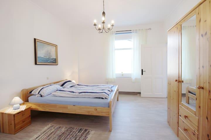 Schlafzimmer zum Hof mit Doppelbett, Kleiderschrank, stabilem Schlafsessel* und Zugang zum eigenen Badezimmer.  (*Foto ist in Arbeit)