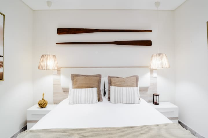 """Second room also thematically decorated: """"the sunset over the dunes"""". Fishermen original wood oars suspended on the bed´s wall."""