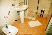 bagno grande, spazioso, con doccia grande, bidet, lavabo, water, appendi accappatoio e asciugamani.
