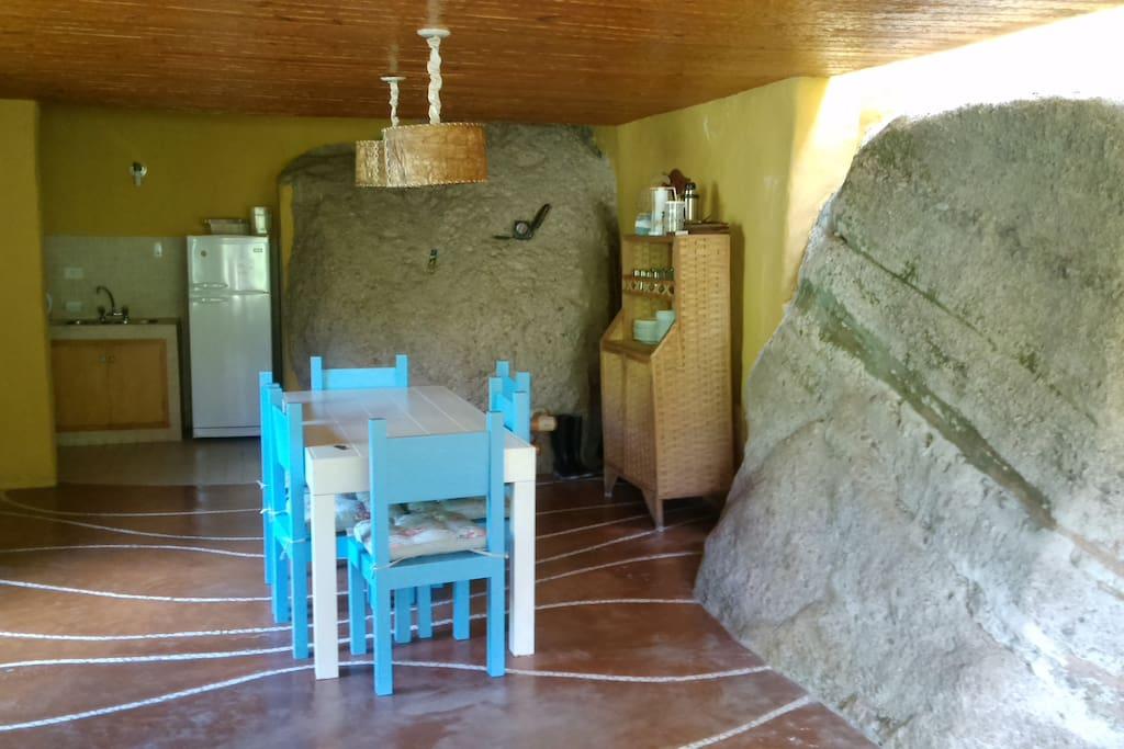comedor y cocina de Casa 0, las rocas gigantes son parte de la montaña que se respetó en la construcción
