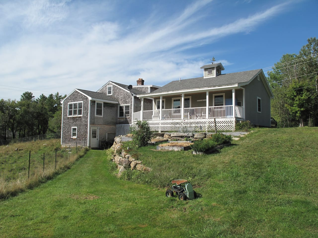 Here the guest porch is featured overlooking nature pond,  goat pasture and view of Mt. Sunapee