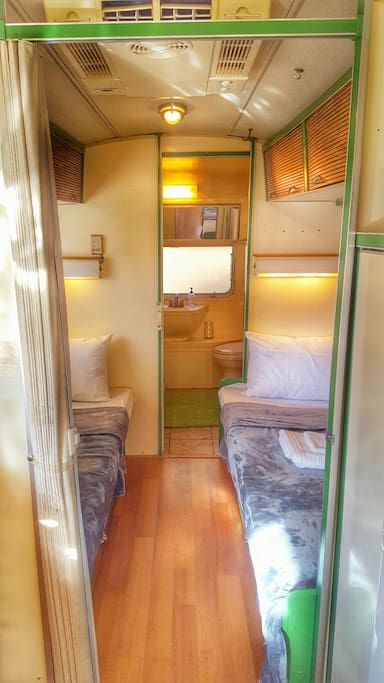 the two twin beds in the trailer on the way to the bathroom in the back
