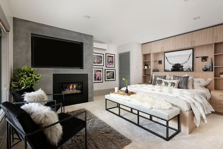 Captivating master bedroom featuring gas fire place, private master bathroom, king size bed, and private entrance leading to pool and hot tub