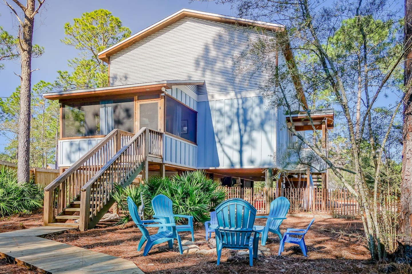 Welcome to Blue Bayou. Here is the back of the house facing the bayou. Enjoy grilling out, make s'mores on the bonfire, sit by the dock, or swing or hammock on the screened in porch!