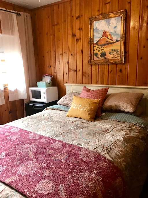 Small cozy sleeping cabin fits queen bed with small refrigerator and microwave, plus table, a chair and coffee pot.