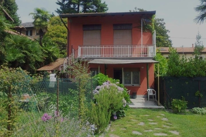 Villa a due piani con giardino, lago e montagna.