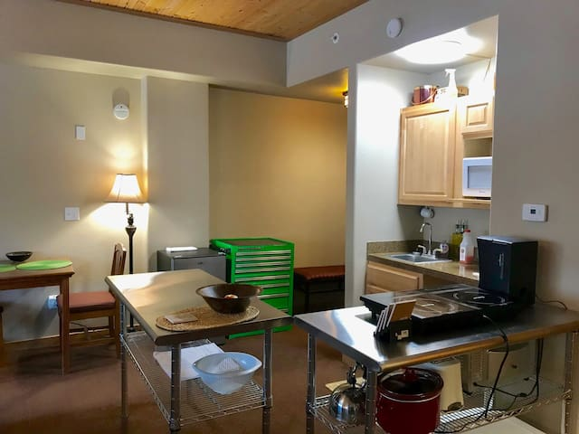 Kitchenette area has microwave, toaster oven, induction stovetop, toaster, coffee maker, cooking pots, dishes, dishwasher and fridge.