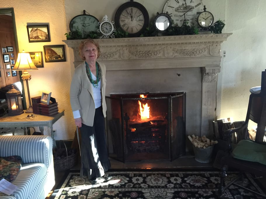 Host, Carol, in front of the living room fireplace