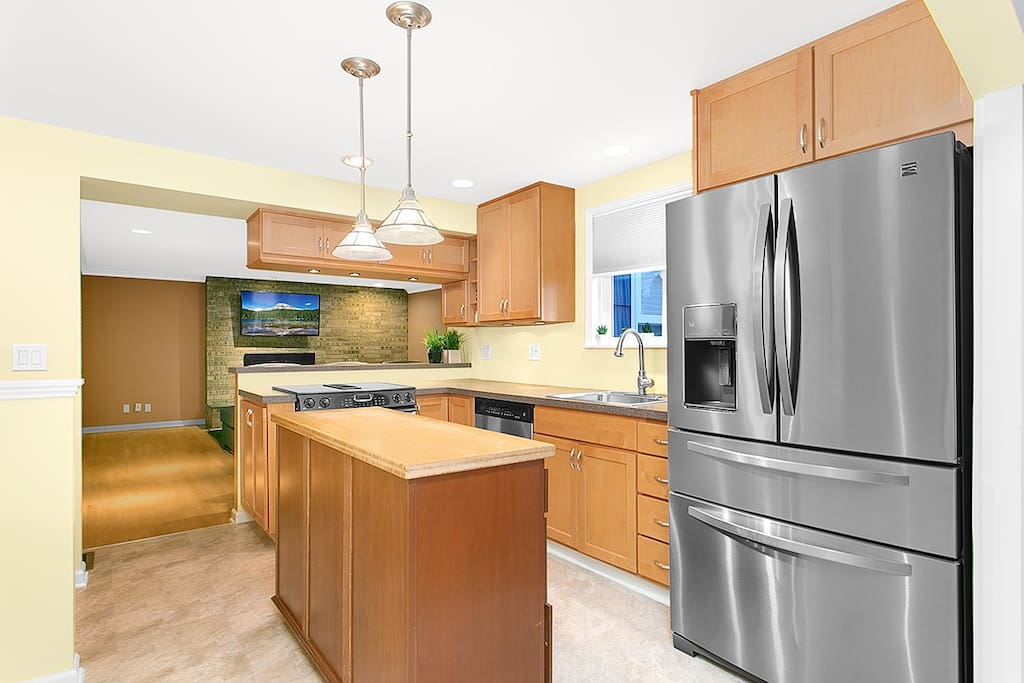 Open kitchen, including coffee maker, pots, pans and dishes.