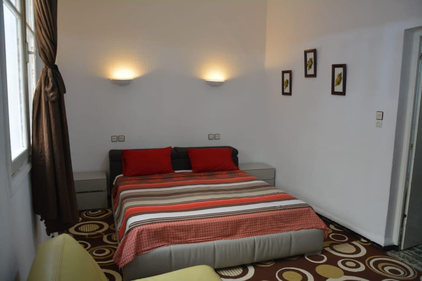 Chambre à coucher spacieuse avec lit en 180 cm et armoire encastré.