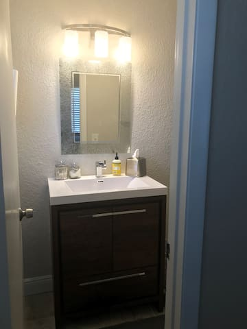 Modern en-suite bathroom with vanity and mirror.