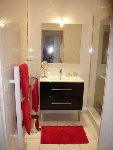 Faux plafonds avec spots, meuble moderne, chauffage sèche serviettes.