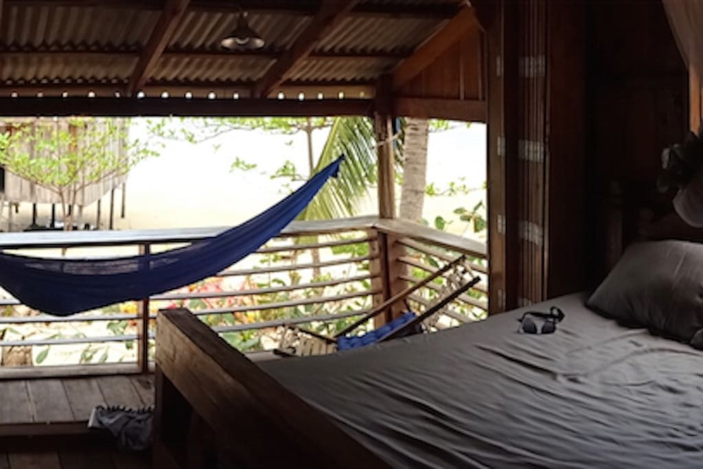Beachfront bedroom faces out to island and steps directly onto the beach.