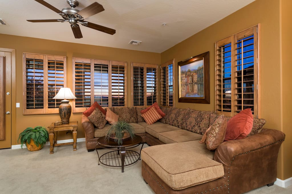Huge wrap around windows in the living room with wood shutters in the entire unit.