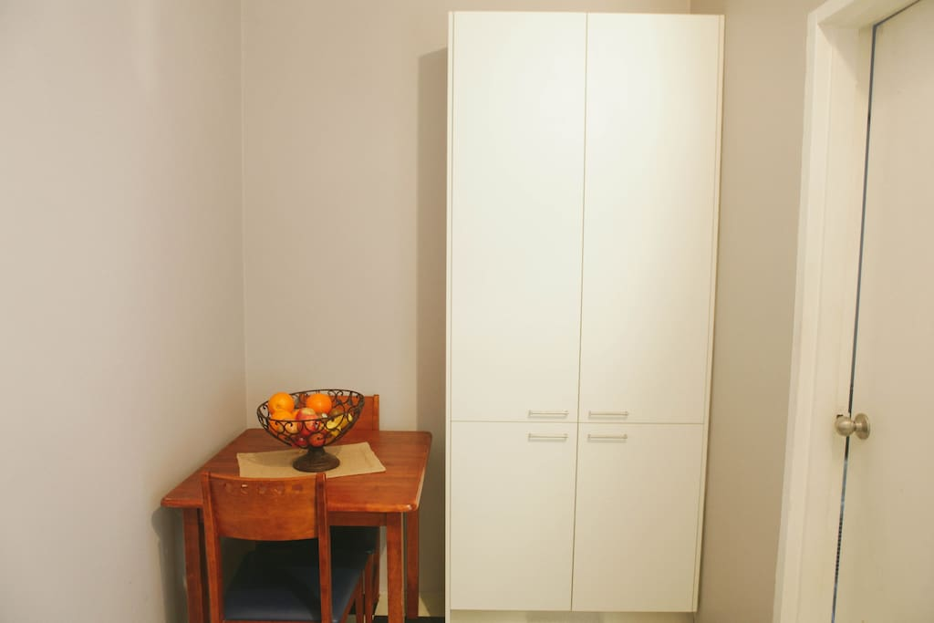 Part of the kitchen, breakfast table & 2 chairs, pantry cupboard, door to internal laundry & washing machine & dryer.