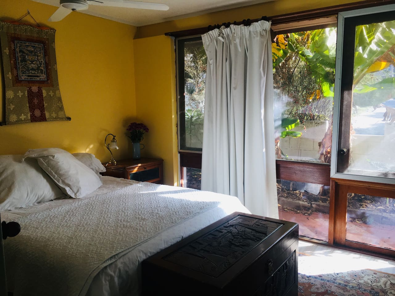 Comfortable queen size bed overlooking tropical pathway