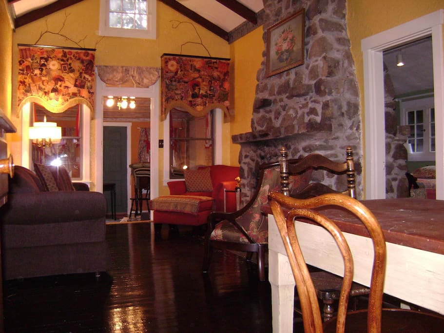 The great room features a wood burning fireplace and 14 ft high ceilings. This large room has a harvest table for dining and conversation plus cozy spaces for reading or just hanging out.