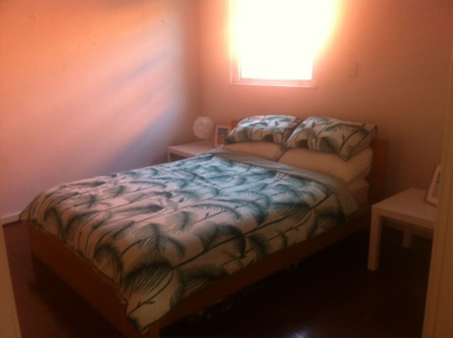 Queen size bed in large bright bedroomwith wardrobes.