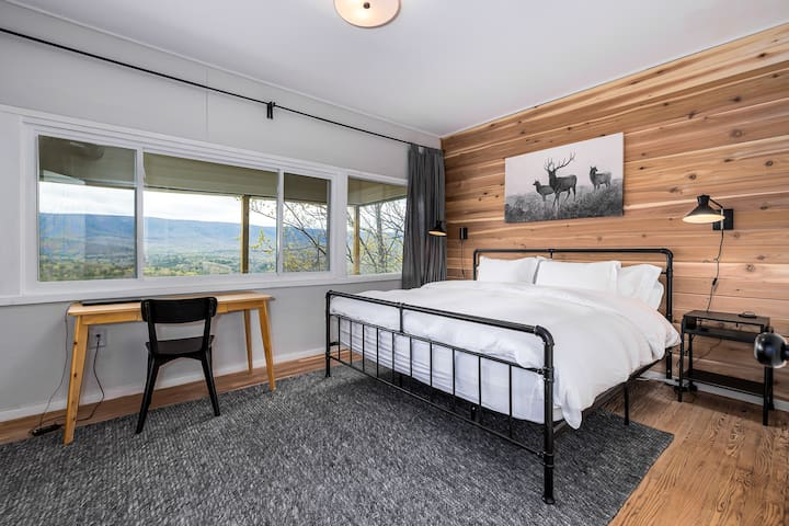 """The second King Bedroom is a large room with a wall of windows highlighting the mountain view, a comfortable workspace, a private bathroom and a 58"""" smart TV."""