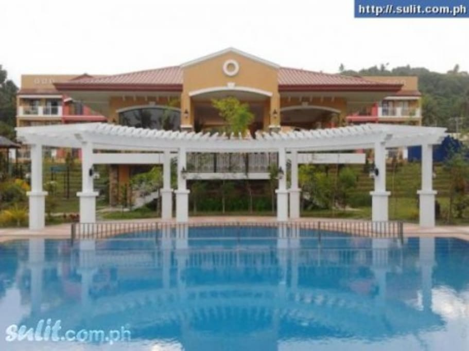 Swimming pool area with showers, gazebo, lounge chairs, children's pool,  and picnic areas.