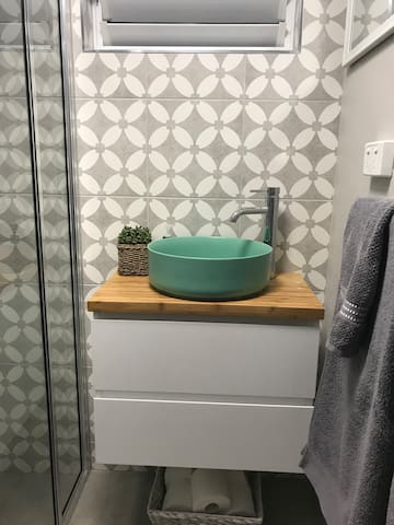 separate bathroom with shower products, shampoo, conditioner, and hairdryer