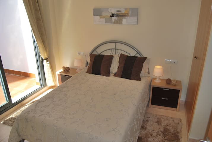 Dormitorio con cama doble, baño en suite, acceso a la terraza y armario integrado