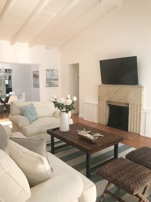 Living Room with high vaulted ceilings, has a very fresh and light ambiance, it has flat screen tv and a fireplace