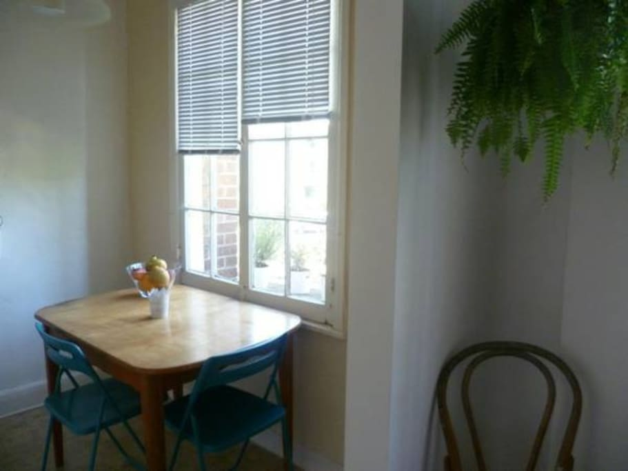 Bright kitchen area with a beautiful, extendable table that sits four people.