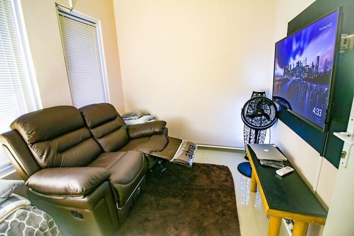 TV room. Used by hosts when house is full but useable from 9am-9pm. Leather recliner couch, tv with chromecast. We have amazon prime and netflix.