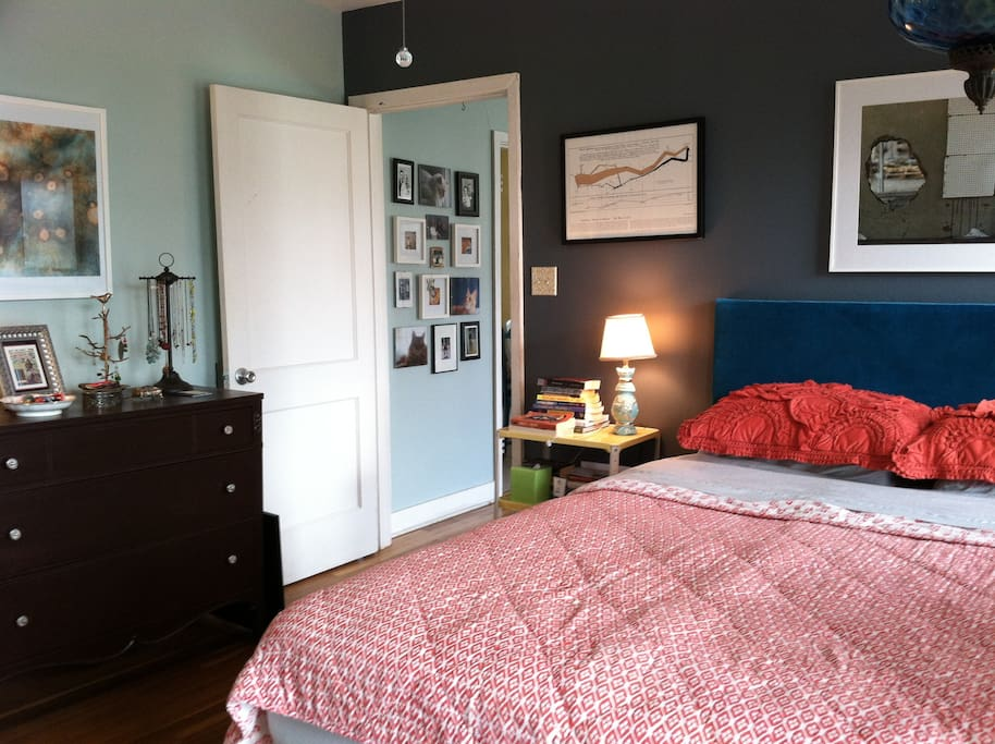 Cozy bedroom with queen sized bed. Plenty of clean sheets and bedding for third guest sleeping on couch.