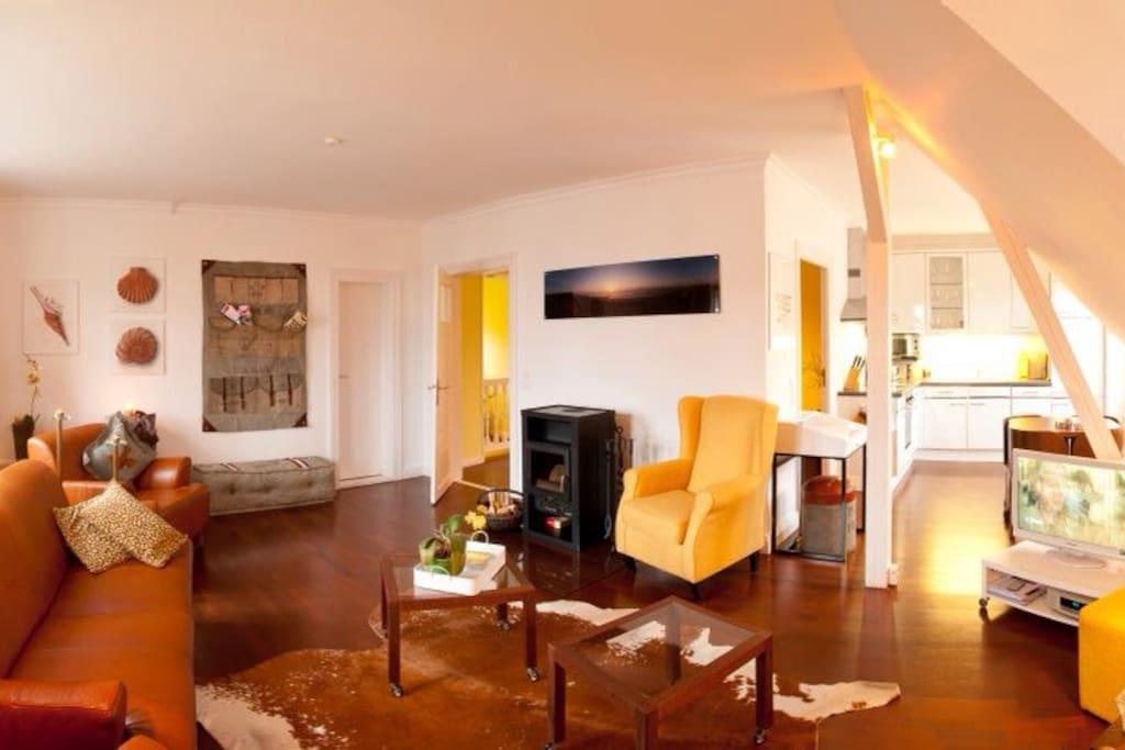 Großzügiger lichtdurchfluteter Wohnraum mit Kaminofen, zwei herrlichen Ledersofas und geräumige, offene moderne Küche mit guter Ausstattung.