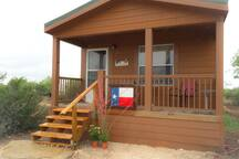 The cabin has a small porch to enjoy the many amenities of the ranch.
