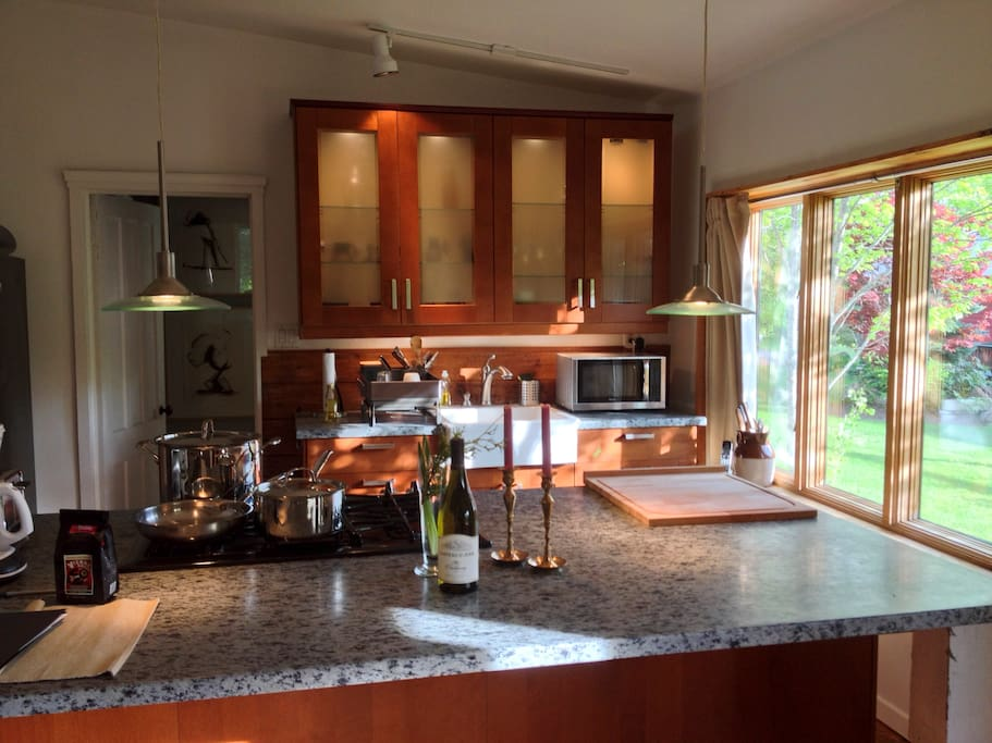 Our well equipped, sun filled kitchen with granite island and built-in large stainless stove/oven is a delight!