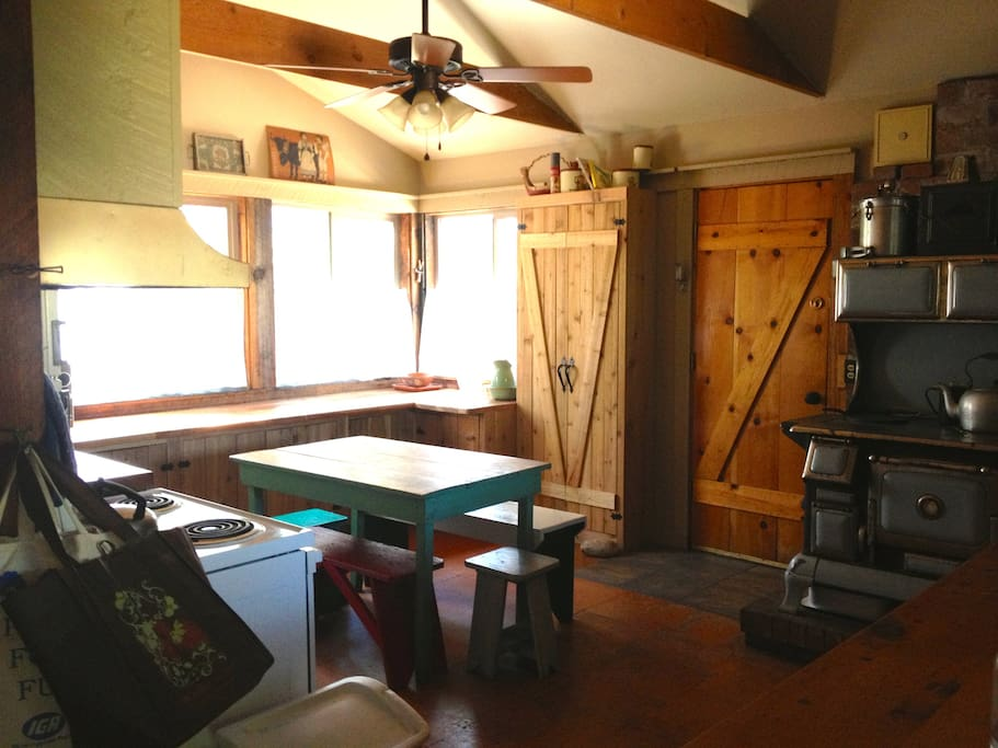 Large kitchen with views of the meadow, lake and back yard has electric stove, microwave, coffee maker, and original woodburning stove.