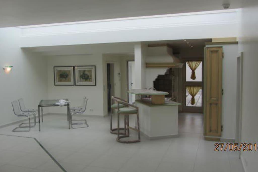 Das Wohnzimmer mit den Bereichen Küche und Esstisch, oben ein Oberlicht, beidseitig beleuchtbar.