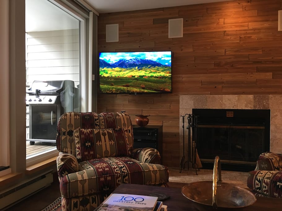 Wood-burning fireplace with cozy chairs and ottoman, 4K TV, Sonos sound system, and view to deck with BBQ, table and chairs