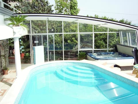 Pool with convertible roof and jacuzzi.