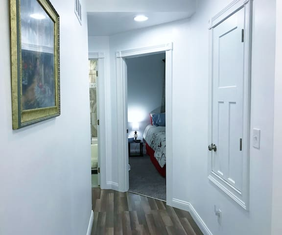 View down the hallway from the kitchen showing the Red Floral bedroom on the right and the full bath to the left!