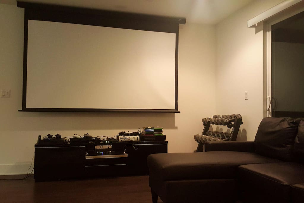 "110"" projector screen, weight lifting rack, Xbox 360 and Xbox One systems"