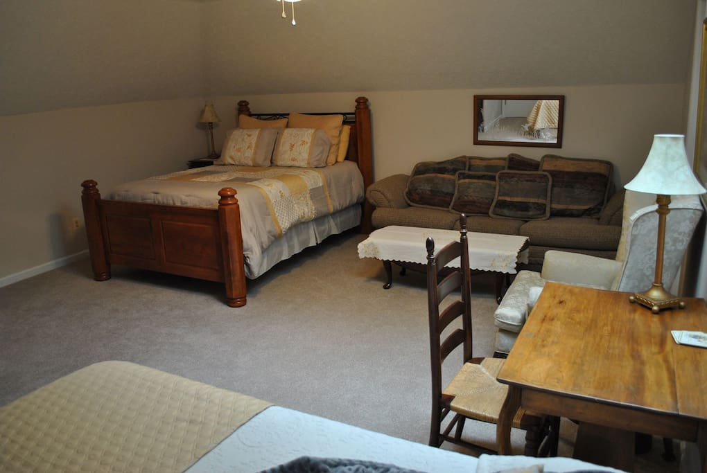 View of room from the full bed showing full sofa and queen bed with desk in the foreground.