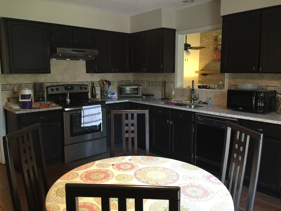 Kitchen equipped with access to stove, refrigerator, dishwasher, microwave and coffee maker.