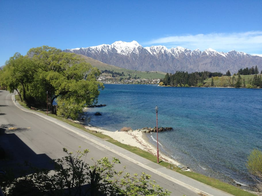 Beach directly across the road and snow on the Remarkables. Photo from house.