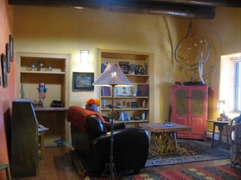 Art-filled living room with hand-made rugs and wood-burning stove