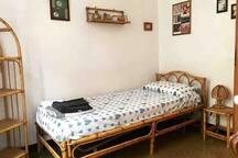 Cameretta da letto singola con cassettiera e scaffale con ripiani.